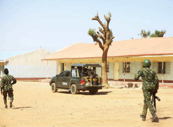 Soldiers comb the surroundings of the school yesterday