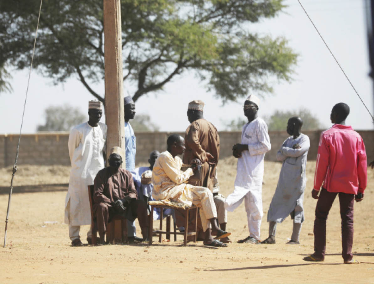Parents wait to hear news about their abducted children outside the Government Science in Kankara, Katsina State yesterday, where gunmen abducted students of the school on Friday night.