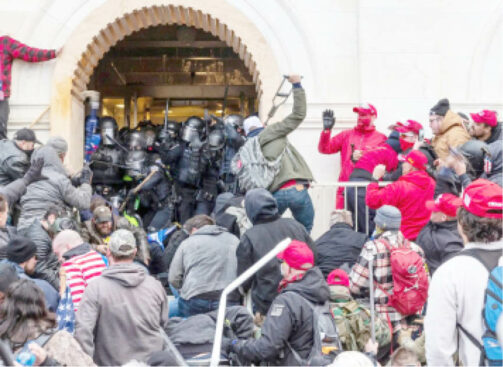Rioters clash with police as they try to enter the Capitol building through the front doors. Rioters broke windows and breached the Capitol building in an attempt to overthrow the results of the 2020 election. Metal bars and tear gas were used Washington DC, US.