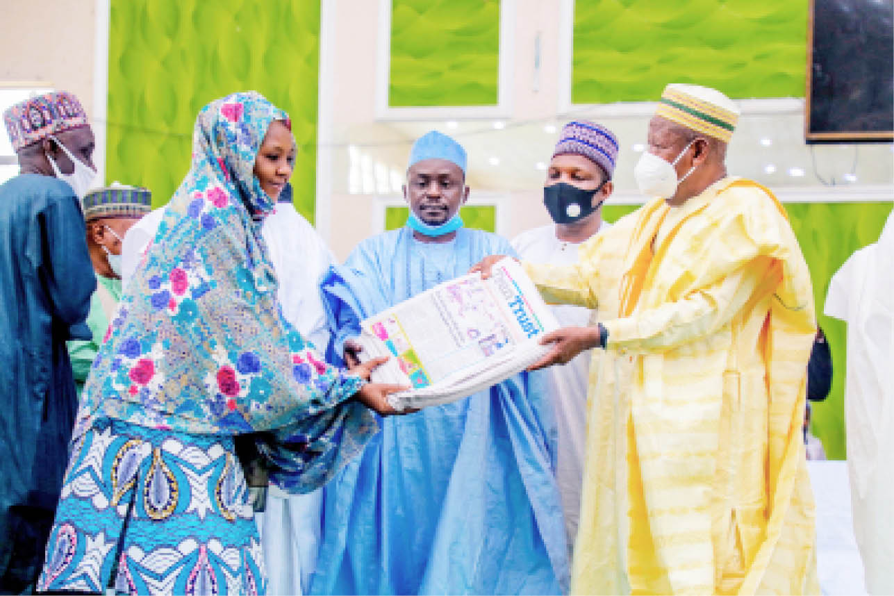 Governor Abdullahi Umar Ganduje presents Teen Trust newspaper to a representative of principals and head of schools in the state